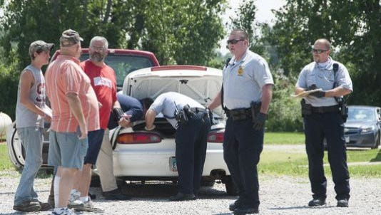 Shelby police investigators in 2013 search the trunk of a car where a dead baby was found. A woman pleaded guilty to abuse of a corpse and an amended count of tampering with evidence.