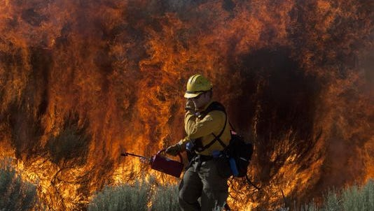 A firefighter covers his face with a gloved hand as he walks along state Route 18 with a dip torch and lights a backfire to contain a wildfire burning west of Diamond Valley in this 2011 file photo.