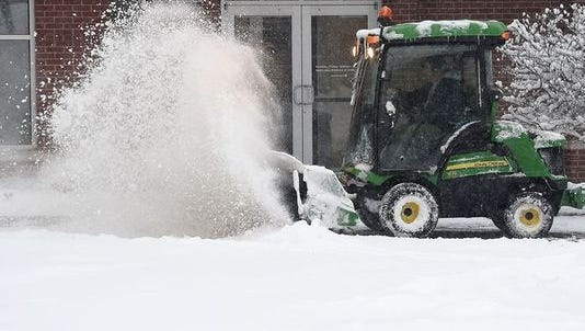 City workers clear snow in Old Town on Dec. 15.