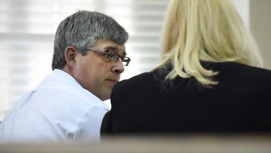Eric Johnson consults with his attorney during his trial.