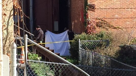 Police examine the body of a man found Nov. 17, 2015 behind a restaurant in Morristown, NJ