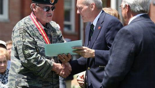 Mine Hill resident Robert J. Guidi, left, receives a distinguished service medal from Morris County Freeholder John Krickus during a Memorial Day ceremony in Morristown in May 2015.  Guidi is accused of receiving benefits and services by embellishing his military record.