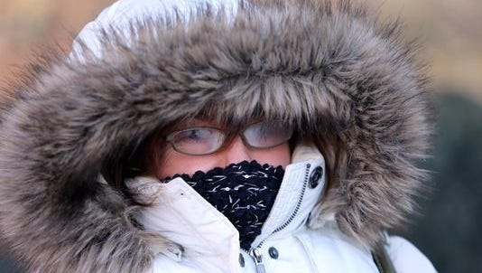 Judy McKendrick bundle up to keep warm from the dropping temperatures Friday morning while waiting for a bus off King Street in downtown Wilmington.