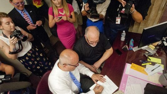 Surrounded by media and well-wishers, Timothy Love, left, signs a marriage certificate as his life partner, Larry Ysunza looks on. The two were the first to apply for a marriage certificate in the Jefferson County Clerk's office following Friday morning's U.S. Supreme Court ruling.