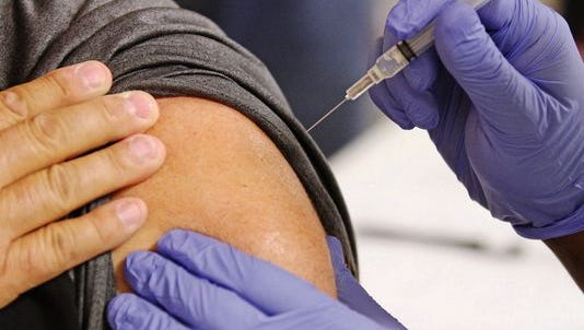 A health care professional administers a flu shot.