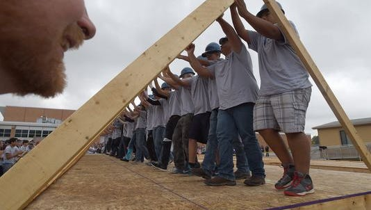 Poudre High School students, teachers, and dignitaries lift up a framed wall Friday for the Nagel family's Habitat for Humanity home in 2014.