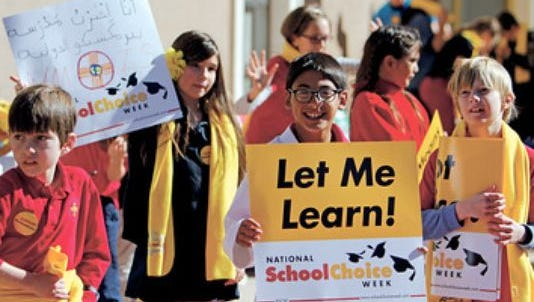 Jack Bensch, 9, a 4th grade student at the New Mexico International School, holds a sign at a rally for National School Choice Week outside of the state capitol on Thursday.