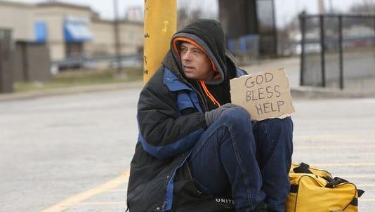 A Springfield panhandler sat between the Walmart and McDonald's restaurant on N. Kansas Expressway in December 2015.