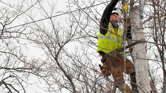 A utility worker tried to restore power in this 2013 photo taken in Lansing. Mid-Michigan had some scattered power outages Friday night that ranged from DeWitt to Leslie.