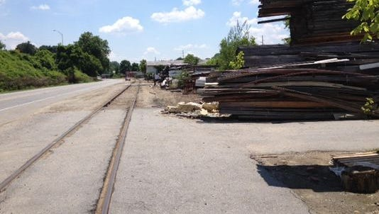 Piles of old lumber have been stacked outside a Riverside Drive warehouse for more than a decade.