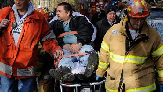 In this photo taken on Sunday, Dec. 1, 2013, Metro North Railroad engineer William Rockefeller is wheeled on a stretcher away from the area where the commuter train he was operating derailed in the Bronx borough of New York. The National Transportation Safety Board reported Monday that the train Rockefeller was driving was going 82 mph around a 30-mph curve when it derailed killing four people and injuring more than 60.