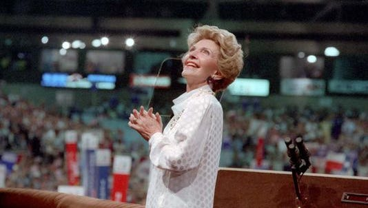 Nancy Reagan looks at President Ronald Reagan on the screen behind her at the Republican National Convention in Dallas on Aug. 22, 1984.
