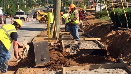 A work crew finishes up a sidewalk in front of the new Publix grocery store this past May. New sidewalks in Swannanoa appear unlikely.