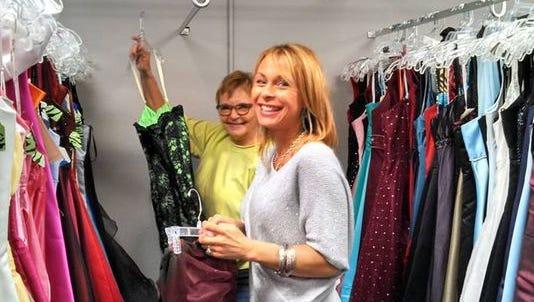 Hollie Heikkinen, right, helps a customer shop for a dress.