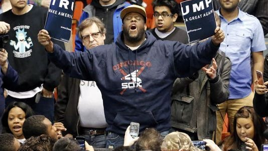 A protester holds up a ripped campaign sign at a Donald Trump rally in Chicago on March 11, 2016