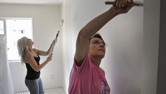 Volunteers Diane Shelander, right, and Jennifer Lesmeister paint the walls of a room in the Women Build Habitat for Humanity project house on Third Street North in St. Cloud in 2014.