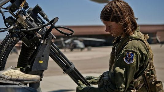 Airman 1st Class Natasha Libby examines the barrels of a Gau-2 mini gun mounted on an HH-60 Pave Hawk helicopter June 20, 2013, at Nellis Air Force Base, Nev.