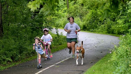 People walk and run on the River Trail in June 2015 just north of downtown Lansing. Ingham County has targeted the River Trail and other pathways for maintenance money  generated by a special millage.