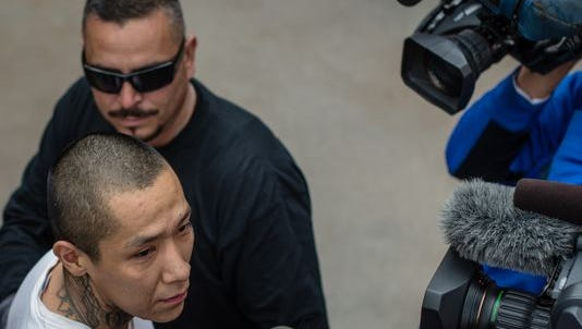 Escaped inmate Lionel Clah, bottom left, is escorted into the State Police office in Albuquerque after being captured Saturday afternoon, March 12, 2016. Police say Clah, the second of two convicts who escaped a prison transport van, surrendered peacefully after being found in an Albuquerque apartment. The other inmate was found on Friday.