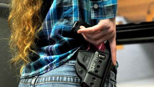 A woman practices unholstering and shooting her handgun during a concealed carry class at On Target shooting range last year.