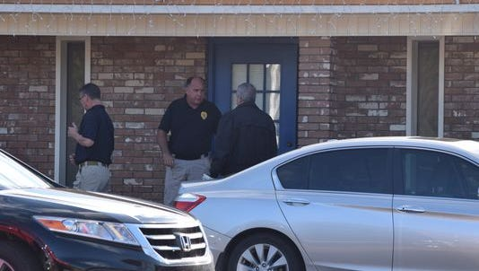 "Investigators stand outside the Pineville law office of Richard Lee on Jan. 15. Lee's body was found inside his office, and autopsy results released on March 21 say he died of a ""self-inflicted injury."""