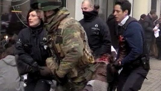 Image from TV hows Belgian policemen and a soldier carrying an injured person after an explosion at the Maelbeek Metro station in Brussels on Tuesday.