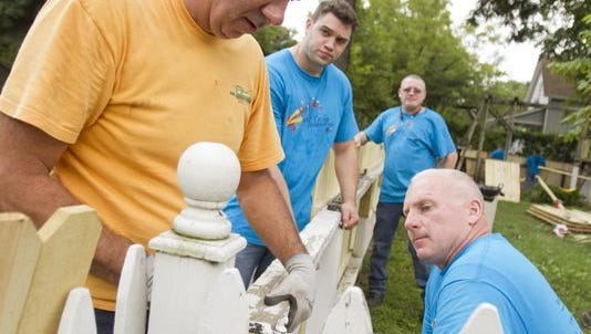 Volunteers build a fence during last year's United Way Day of Caring event. More than 17,000 Livingston County volunteers took part.