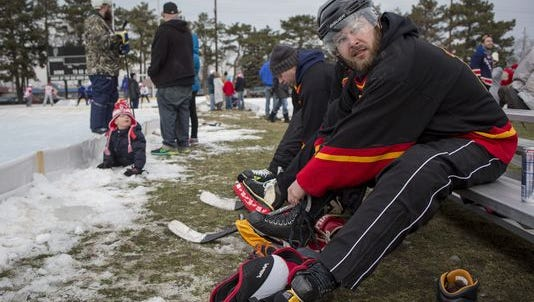 Mama Vicki's Coney Island team member Lance Thorpe ties up his skates during a pond hockey tournament Saturday, Jan. 30, 2016 at Memorial Stadium in Port Huron.