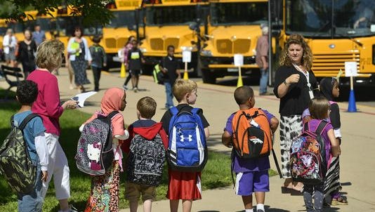 Students wait with their teachers at Oak Hill Community School before being led to the correct buses Tuesday on the first day of school in 2014 in St. Cloud.