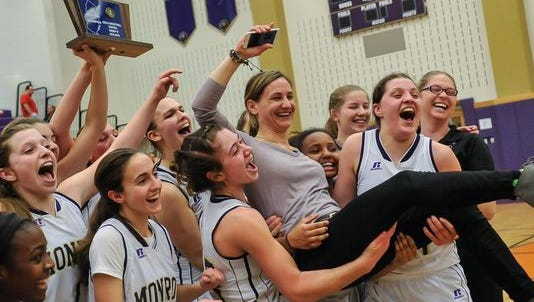 The Monroe girls basketball team celebrates with head coach Leigh Vogtman after defeating Hunterdon Central 48-35 in the Central Group IV sectional final at Monroe High School on Mar. 8, 2016