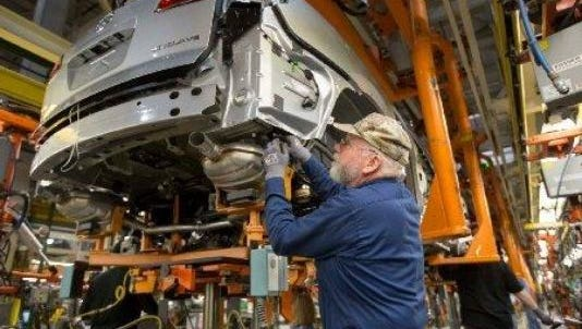 A UAW employee works on a Buick Enclave at the Lansing Delta Township Assembly plant. The plant will shutdown for over a month in May for retooling and new equipment.