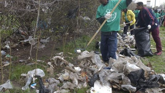 Volunteers clear out a vacant lot at Eugene and Conner on Detroit's east side in 2004 during Motor City Makeover.