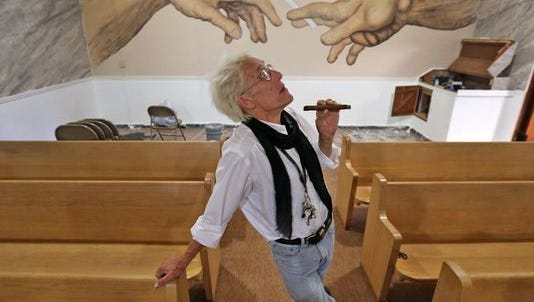 "Bill Levin poses in the sanctuary at The First Church of Cannabis on June 23, 2015. The sanctuary, still under renovation, includes a painting on the back wall of two hands passing a cannabis cigarette. The painting, by CS Stanley, the church's minister of art, is similar to a detail of Michelangelo's ""Creation of Adam"" painting on the Sistine Chapel ceiling."