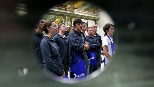 Students from Centerville High School are seen framed using a part used to make an aircraft bulkhead while watching a demonstration during National Manufacturing Day at Makino in Mason. Makino opened its facility to more than 500 students and local community visitors to encourage, educate and promote youth interest in manufacturing careers.