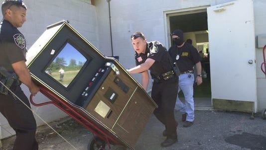 Buncombe County Sheriff deputies remove an illegal video poker machine in 2007.