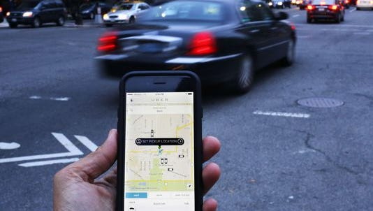 An Uber application is used to hail a ride.
