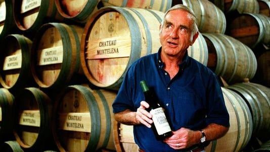 Jim Barrett, owner of Chateau Montelena, holds a bottle of the 1973 Chardonnay that won the 1976 Paris Tasting, while standing by barrels in the winery's cellar in Calistoga, Calif., in 1996.