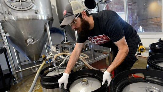 Sawyer Stevens, head brewer at Lansing Brewing Company, moves around kegs as he fills them with Amber Cream Ale in August. The Brewery will distribute three beers to 20 bars in the region starting in June 2016.