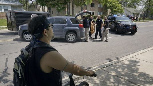 Neighbor Jose Valdez watches Westland Police officers at the scene of a shooting in the 34000 block of Glenwood Thursday morning. One man was killed, a second wounded and two others taken into custody.