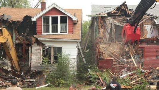 Demolition crews tear down abandoned houses on Turner Street in Detroit on August 26, 2013.
