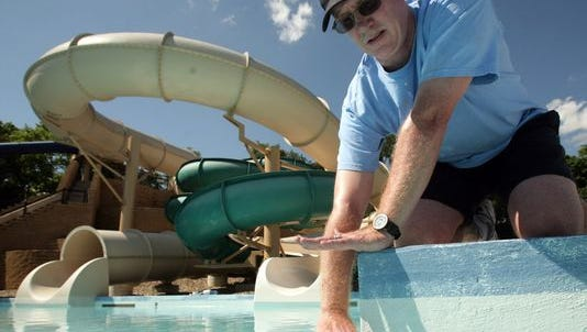 Mark Brewick, recreation supervisor, demonstrates how much a leak at West Des Moines Holiday Park Aquatic Center dropped the water level in 2007. Park officials discovered a similar leak this year, which delayed the pool's opening by 16 days.