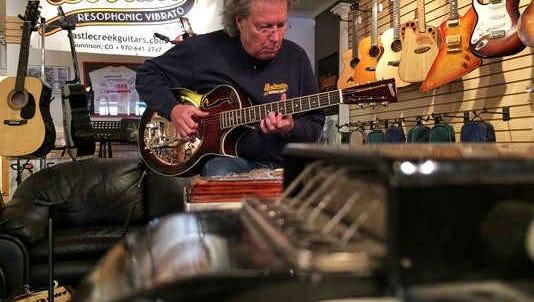 Kent Viles plays inside his Gunnison guitar shop.