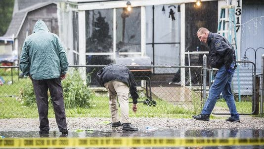 City police investigators at the scene of a fatal police-action shooting on West 18th Street on Saturday.
