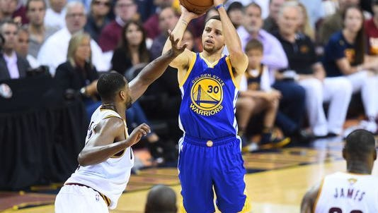Golden State Warriors guard Stephen Curry shoots a three-pointer.