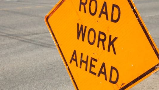 Road work ahead sign against asphalt road.