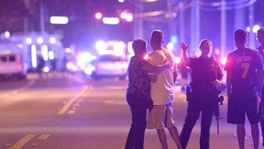 Police officers direct family members away from a multiple shooting at a nightclub in Orlando, Fla.