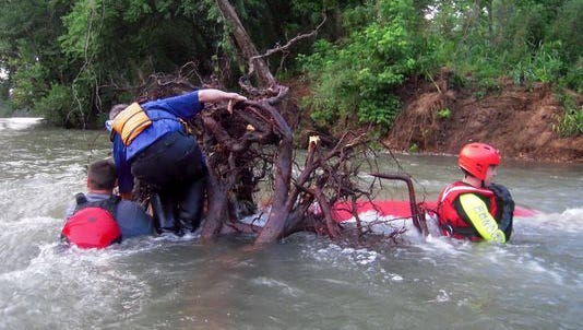 Emergency responders work to free a canoe pinned against a root wad in the Buffalo National River on June 12.