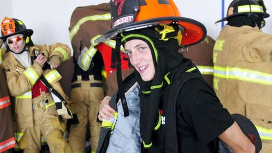 A participant at the 2015 Junior Firefighter Academy puts on his uniform.