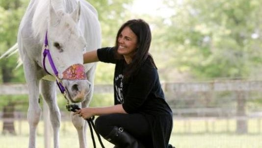Tracey Stewart kneels besides Lily the horse who died over the weekend.