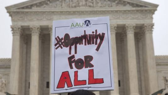 American Association of University Women holds a sign outside of the Supreme Court in Washington, D.C.